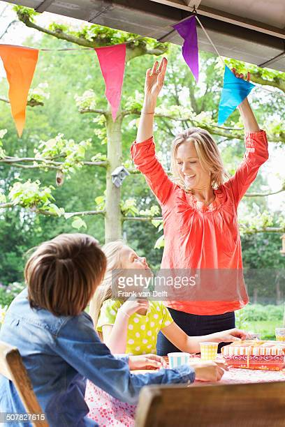 Mother chatting with children and putting up bunting
