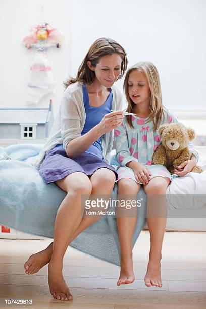 Mother checking daughters temperature with digital thermometer