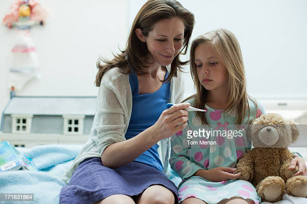 Mother checking daughter's temperature with digital thermometer