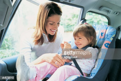 Mother Checking Her Toddler's Child Seat in a Car