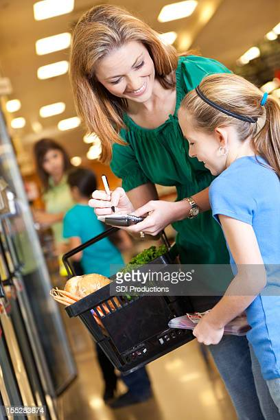 Mother checking list and coupons with daughter while grocery shopping