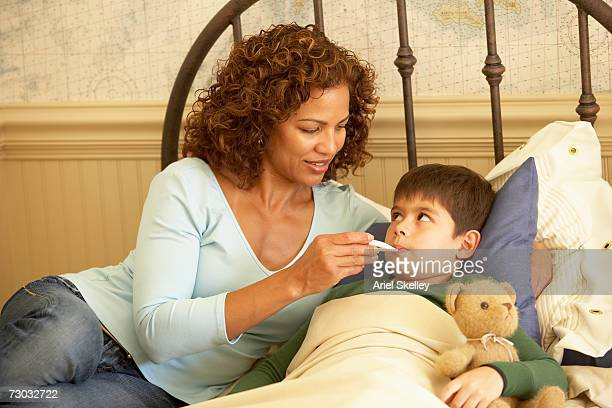Mother checking son's (6-7) temperature on bed