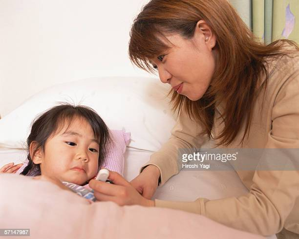 Mother checking temperature of her daughter