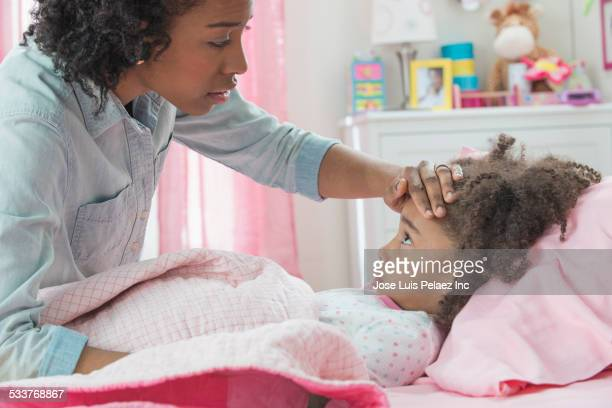 Mother checking temperature of sick daughter