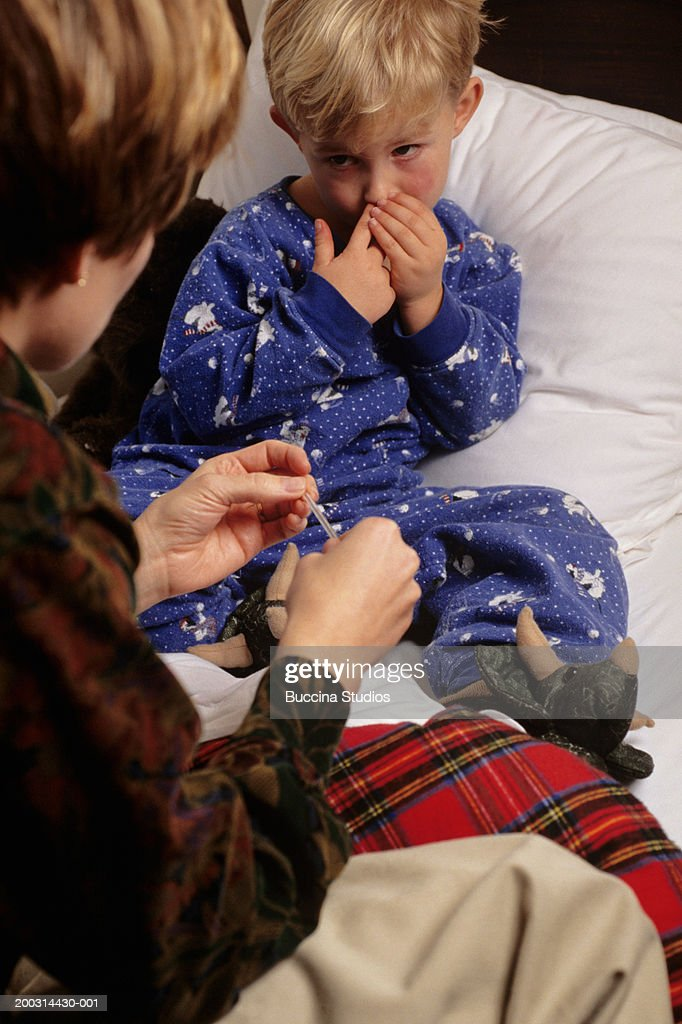 Mother checking temperature of son in bedroom stock photo for Bedroom temperature