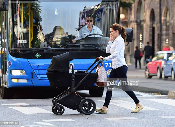 Mother, child in stroller, crossing street, bus and traffic background