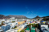 Elevated view of Cape Town with colourful houses in the foreground and Table Mountain and Lion's Head clear blue sky in the background Mother City South Africa