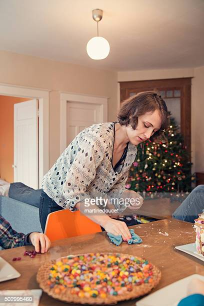Mother cleaning kitchen table at Christmas time.
