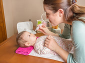 Mother cleaning mucus catarrh of adorable baby with a nasal aspirator