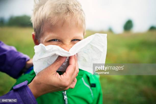 Mother cleaning nose of sick boy
