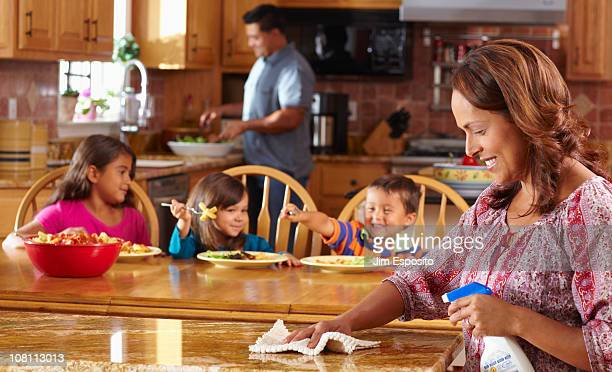 Mother cleaning while children eat in background