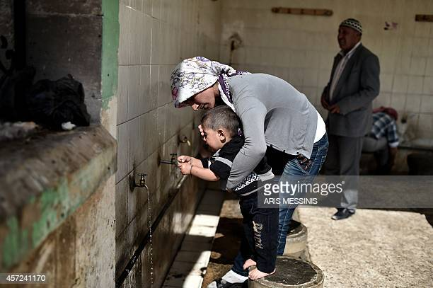 A mother cleans the face of her child as Syrian Kurdish refugees take shelter in a mosque in the Turkish town of Suruc in the Sanliurfa province on...