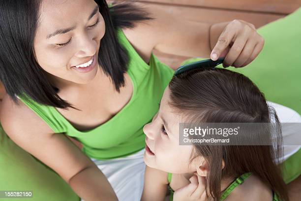 Mother combing daughter hair