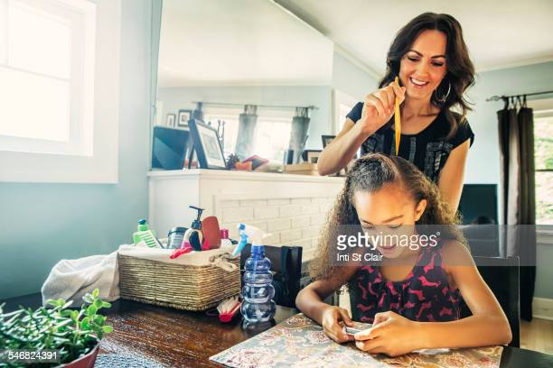Mother combing hair of daughter at kitchen table