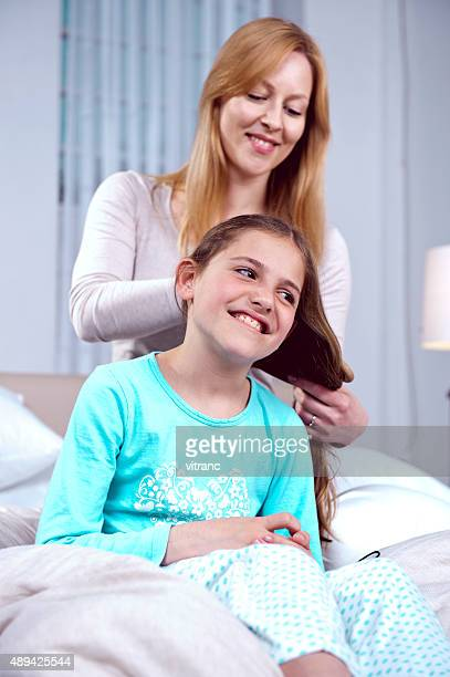 Mother combing hair of daughter