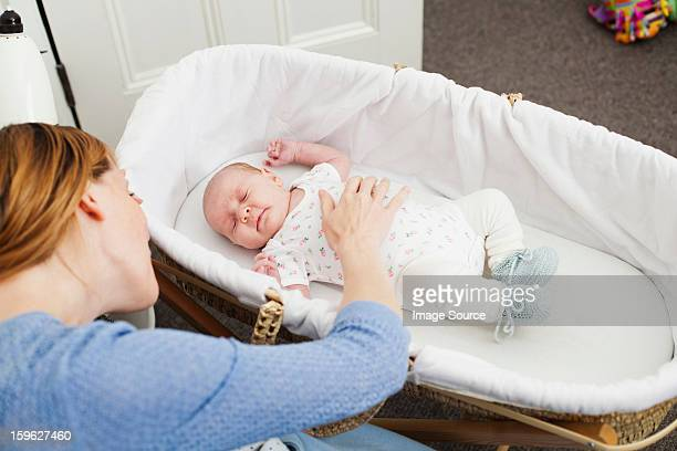 Mother comforting newborn daughter in bassinet