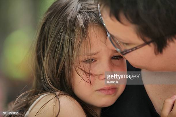 Mother comforting teary young girl