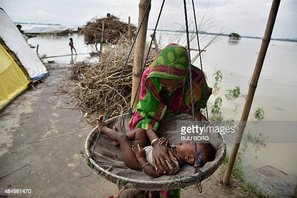 A mother comforts her son at a temporary shelter in the flood affected Morisutitop village in the Morigaon district of north eastern Assam state on...