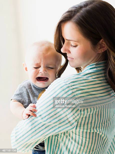 Mother consoling baby boy (6-11 months) indoors