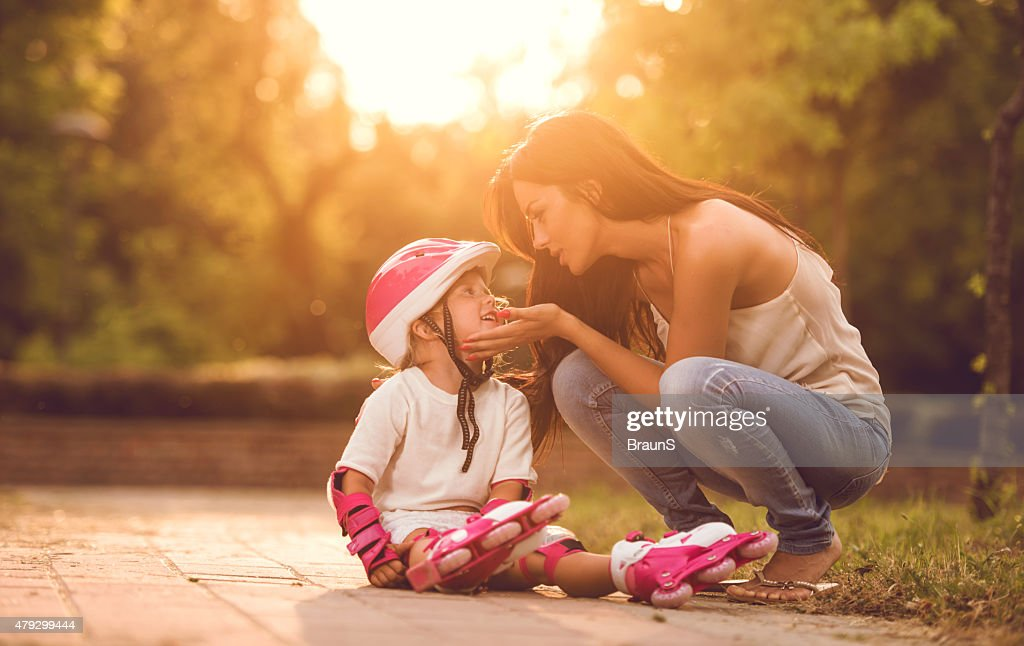 Mother consoling her daughter who fell while driving rollerblade. : Stock Photo