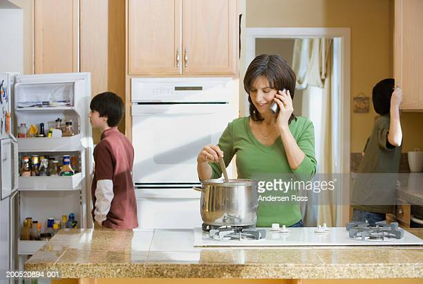 Mother cooking and talking on phone, two sons (12-14) in background