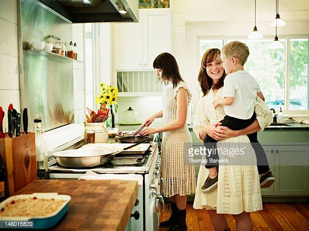 Mother cooking in kitchen while aunt holds nephew