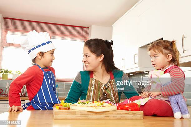 Mother cooking with children in kitchen