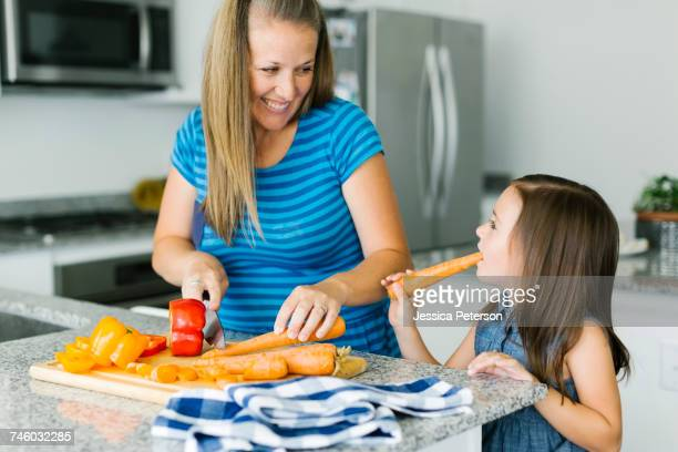 Mother cooking with daughter (6-7) in kitchen