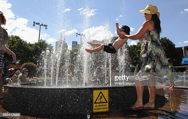 A mother cools off her son in the fountain at Garden Square during day one of the 2016 Australian Open at Melbourne Park on January 18 2016 in...