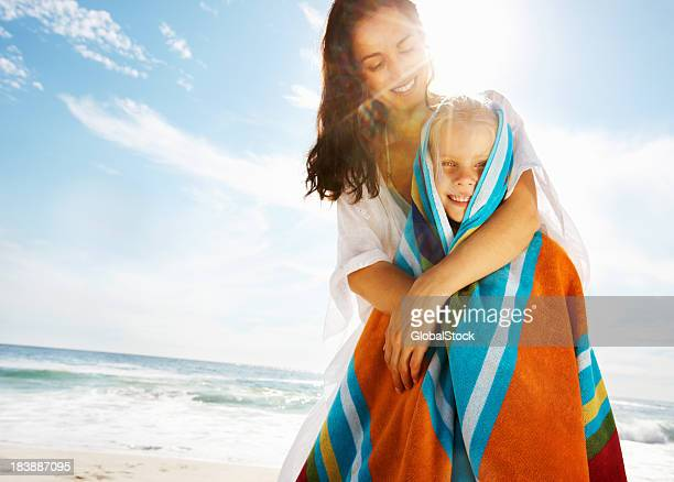 Mother covering daughter with towel on the beach