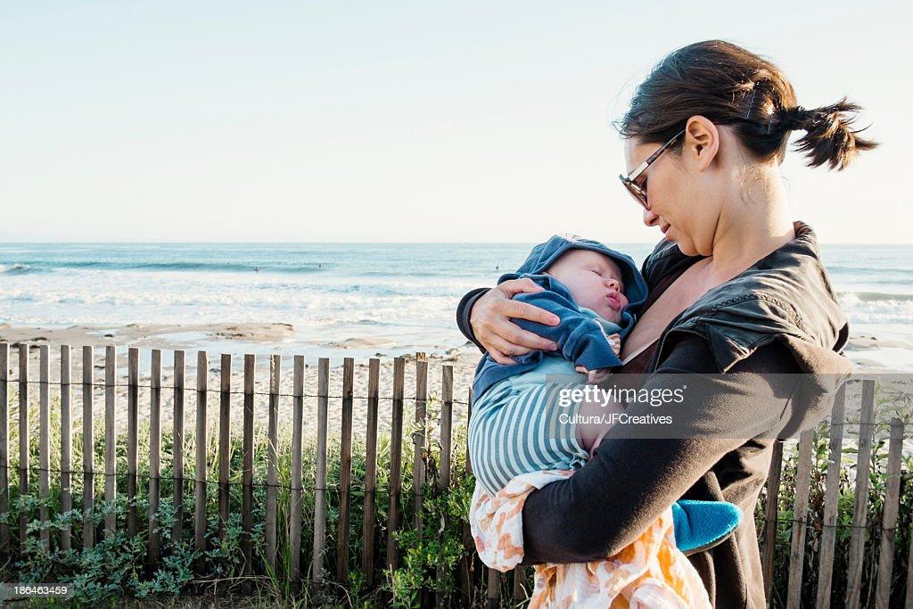 Mother cradling sleeping baby at coast
