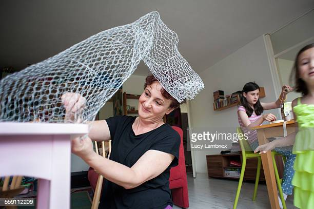Mother crafting a horse from chicken wire