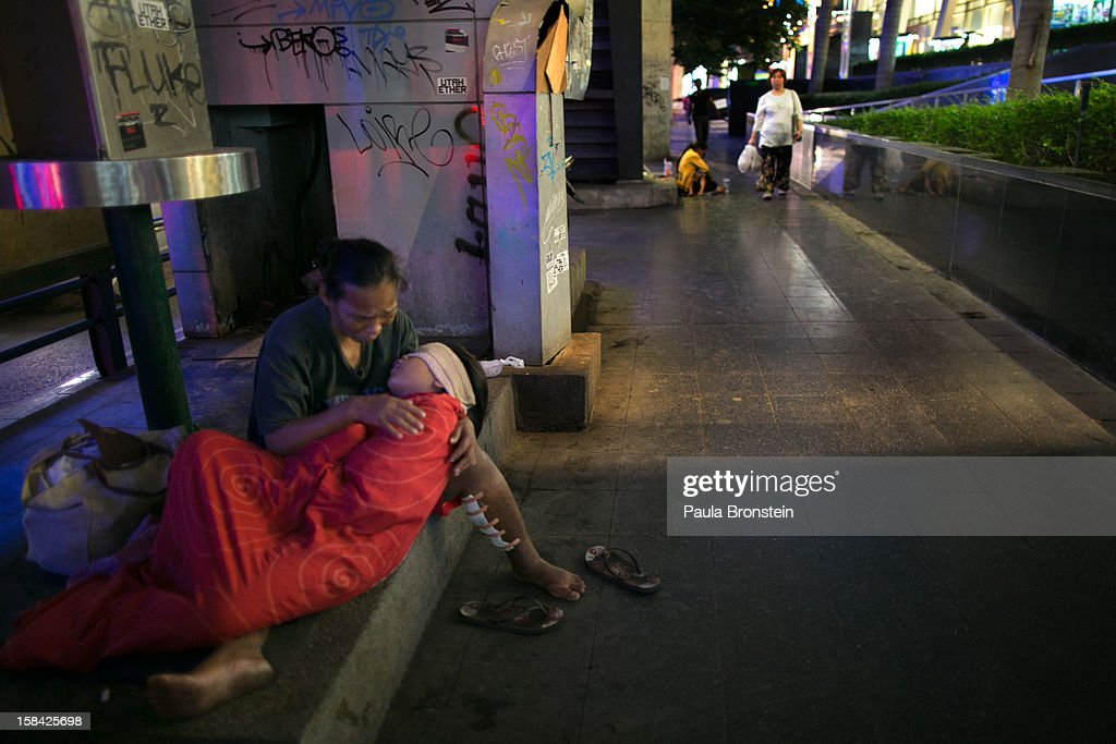 A mother cries as she holds her sick daughter begging for money to take her to the hospital in the main shopping district December 16, 2012 in Bangkok,Thailand.Thailand's high tourist season is booming this year compared to 2011 which was tainted by the flooding as Christmas shoppers visit the shopping malls looking for the bargains.