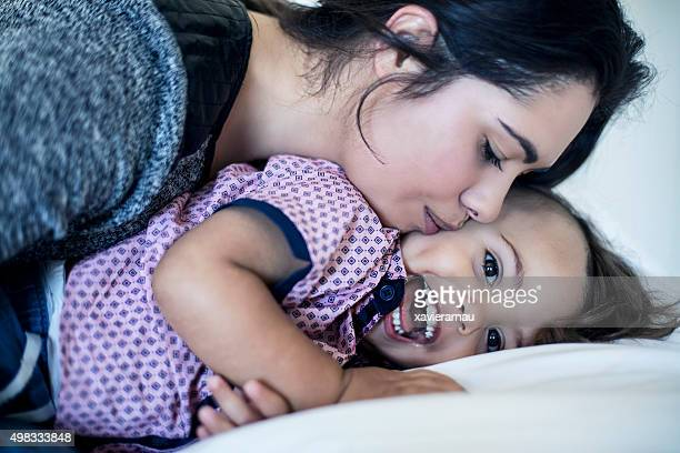 Mother cuddling and kissing her son
