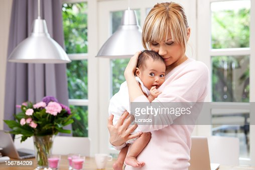 mother cuddling her daughter : Stock Photo