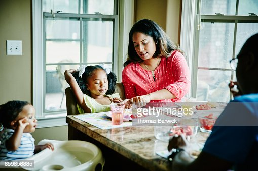 Mother cutting daughters food at breakfast