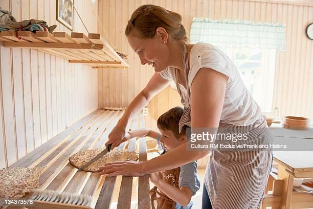 Mother cutting flatbread in kitchen