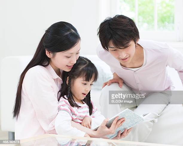 Mother, Daughter And Father Reading Book