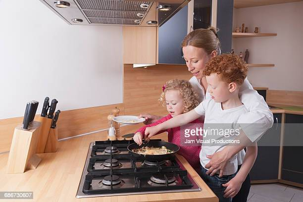 Mother, daughter (4-5) and son (8-9) preparing scrambled eggs together