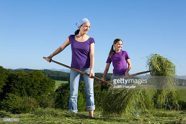 Mother, daughter collecting grass