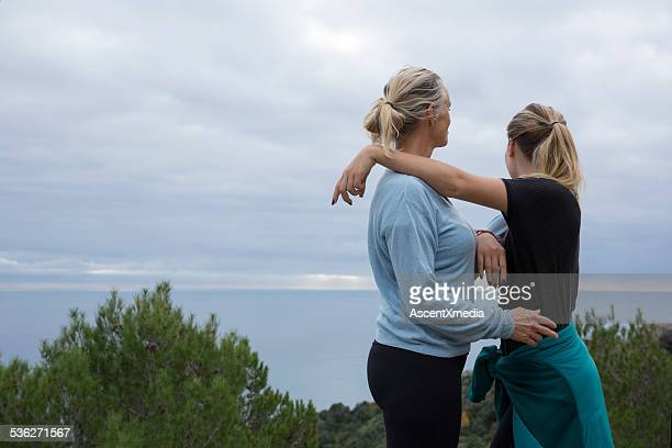 Mother & daughter embrace after hike above sea
