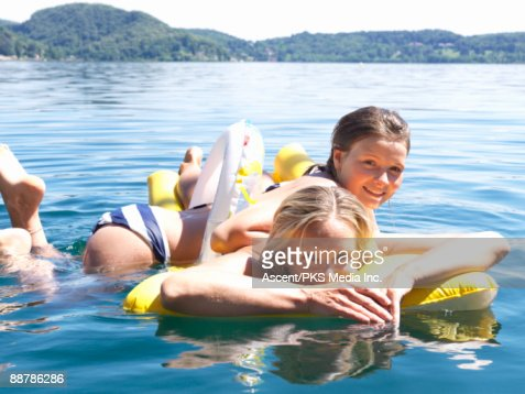 Mother & daughter float on inflatable rafts, lake : Stock Photo