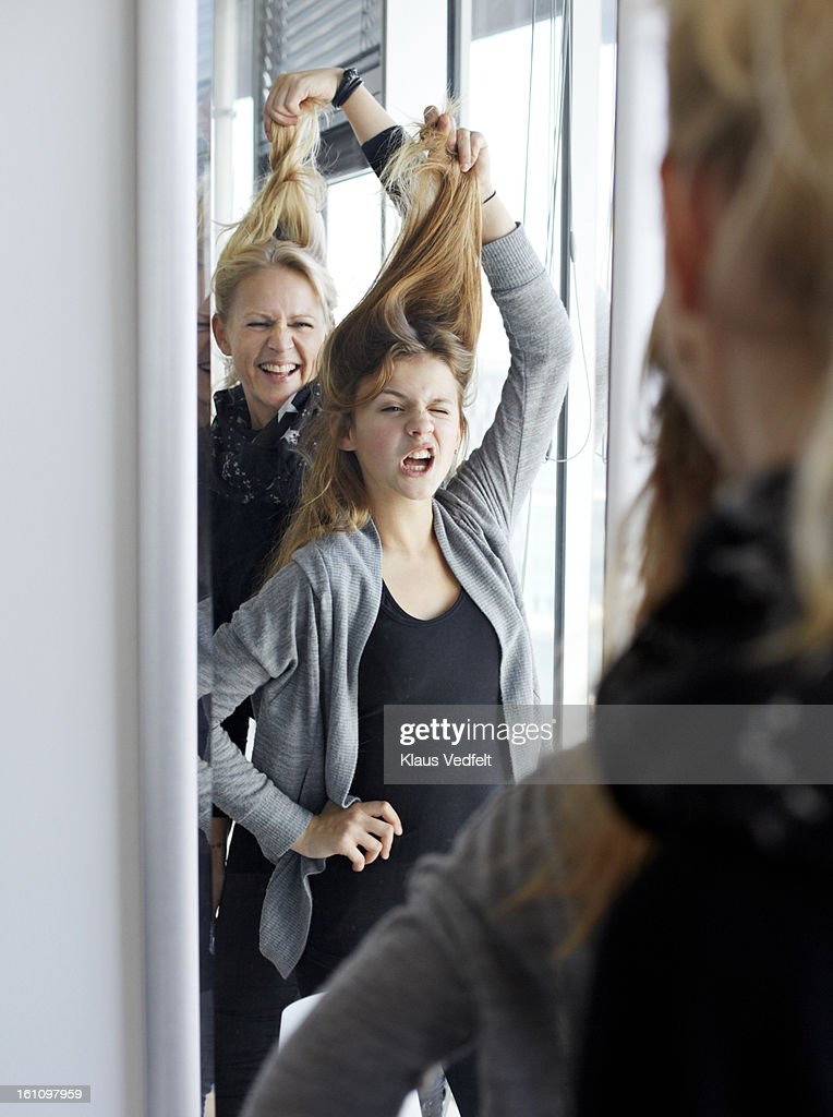 Mother & daughter having fun in front of mirror : Stock Photo