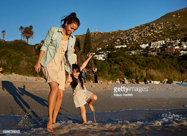 Mother & daughter paddling in the water at beach