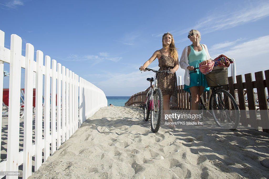 Mother & daughter push bikes along sand, from sea : Stock Photo