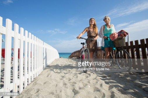 Mother & daughter push bikes along sand, from sea : Bildbanksbilder