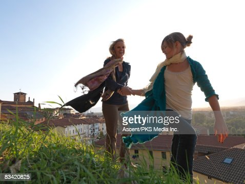 Mother & daughter walk in wind above town : Stock Photo