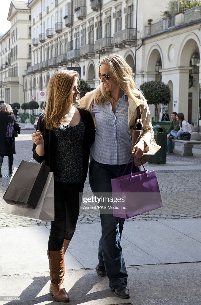 Mother & daughter walk thru piazza, shopping bags : Stock Photo