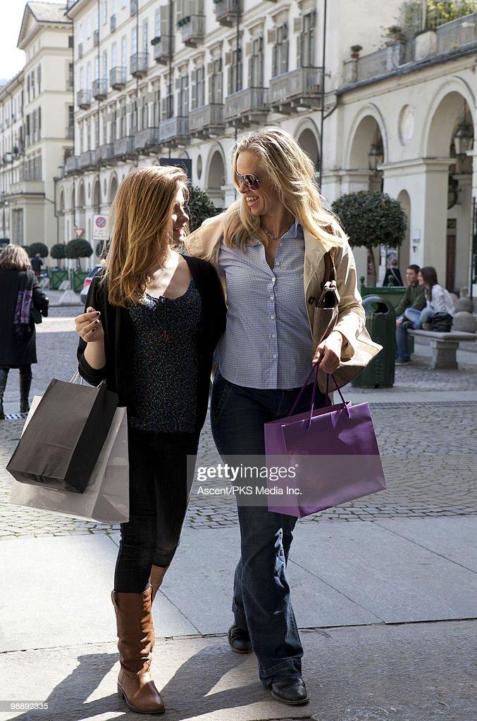 Mother & daughter walk thru piazza, shopping bags : Bildbanksbilder