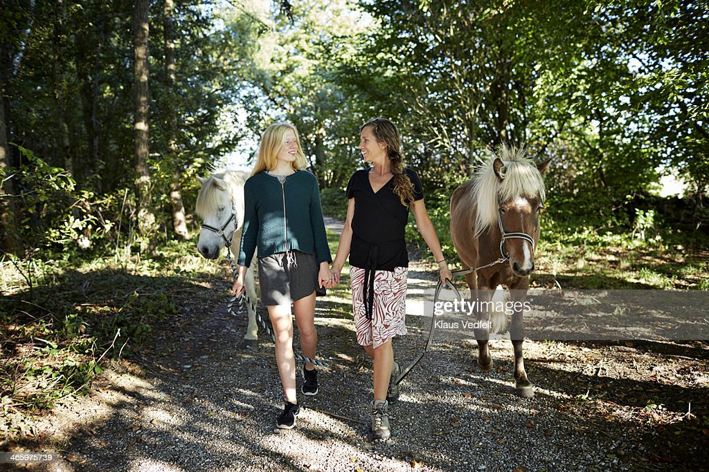 Mother & daughter walking with horses : Stock Photo